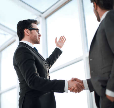close up of a businessmen shaking hands during a conversation in the office