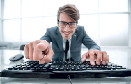 man pointing at something with finger and using computer keyboard