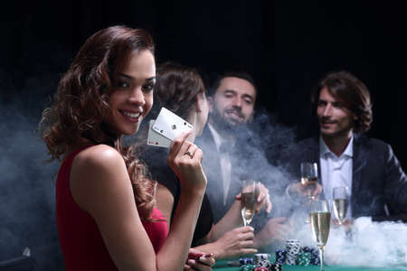 young brunette woman holding poker cards and playing poker with her friends