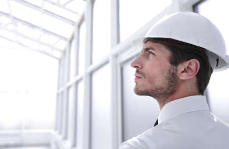 architect in protective helmet standing in empty office Stock Photo