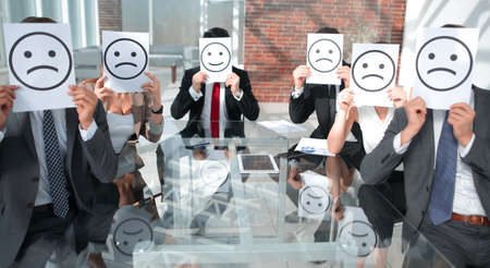 Image of business people holding drawing of upset face.