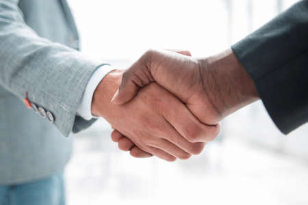 Business handshake in lofty office