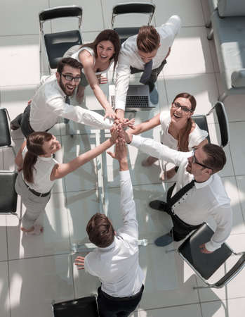 top view.the companys employees are giving each other high five
