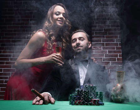 Couple in the casino playing poker on green felt Reklamní fotografie