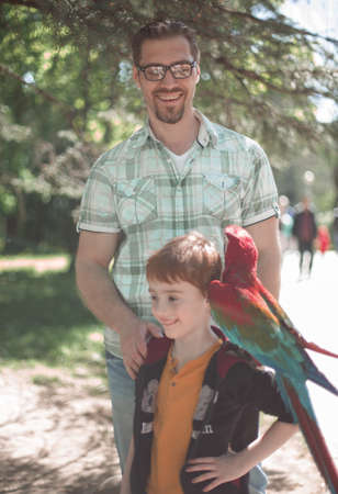 Portrait of father and son with macaw parrot
