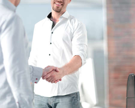 handshake of business people standing in a creative office Stock Photo