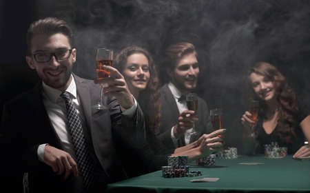 poker players with a glass of wine ,sitting at a table Stock Photo