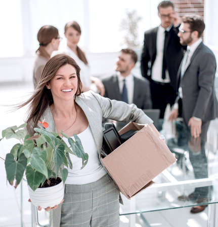 Young happy business woman with boxes for moving into a new office