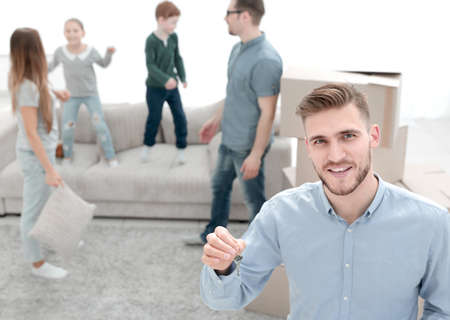 smiling estate agent showing keys from new apartments