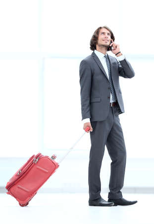 businessman with Luggage talking on a cell phone.