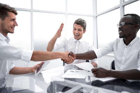 close up.handshake of international business partners at the Desk
