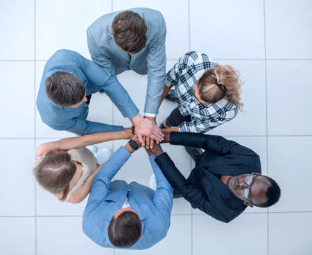 Top view of people putting hands together