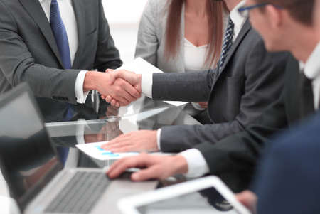 Two businessmen shaking hands with colleagues  on background. Banque d'images