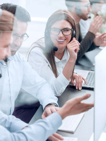 smiling employees of call center talk sitting behind a Desk