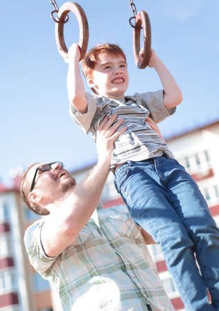 father teaches his son to catch up on the bar.