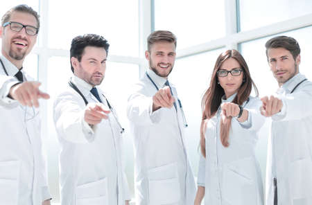 group of practicing doctors pointing their finger at you Фото со стока