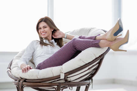 happy woman sitting in comfortable chair 스톡 콘텐츠