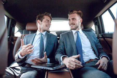 business colleagues talking, sitting in the back seat of a car