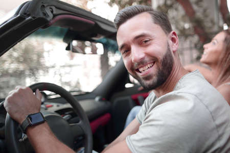 close up.portrait of a smiling man sitting behind the wheel of a convertible car Archivio Fotografico