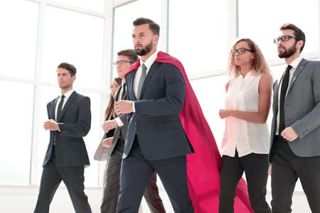 businessman in Superman cloak and business team standing in office lobby
