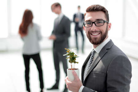 successful businessman with a green young shoot on blurred background