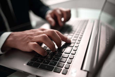 close up. businessman typing on laptop keyboard.people and technology