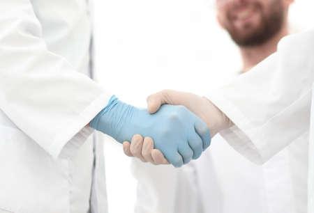 Abgeschnittene Aufnahme von medizinischen Mitarbeitern, die sich die Hände schütteln. Foto mit Kopierraum