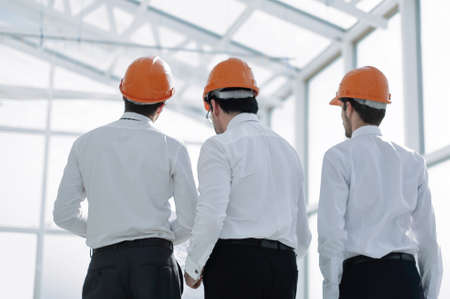 rear view.businessmen in protective helmets standing in the new office.photo with copy space