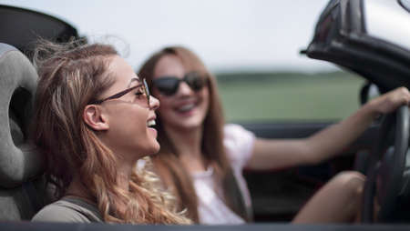 two fashionable girls travel in a convertible car. Фото со стока