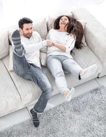 laughing couple having fun on the couch in the living room