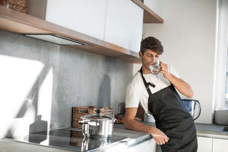 young man drinks clean water standing in the home kitchen
