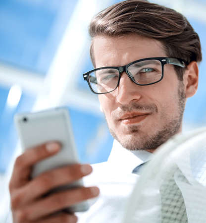 close up.confident businessman with smartphone. Stock Photo