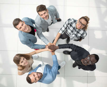 Concept de travail d'équipe. Vue de dessus en grand angle d'un jeune hipster plié les mains empilées sur le dessus