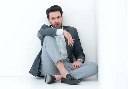 frustrated businessman sitting near the wall.