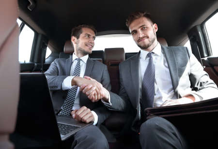 handshake business partners in the car.