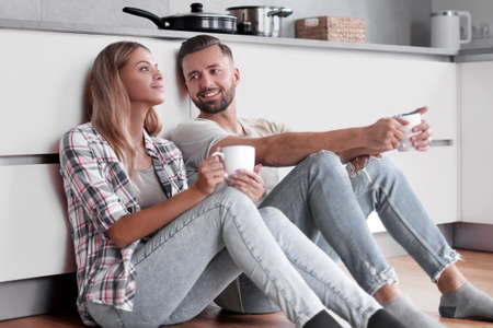 young couple drinking coffee sitting on the kitchen floor