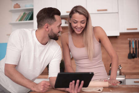 Young couple surfing the web with tablet at home kitchen