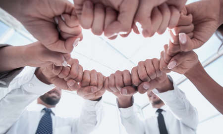 close up. employees of the company forming a circle out of their fists
