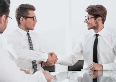 business partners shake hands while sitting at the Desk 版權商用圖片