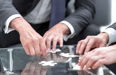 close up.business partners put the puzzle together Imagens - 128862764