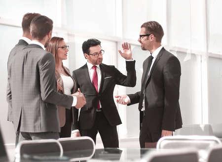 empleados hablando de pie en la oficina.