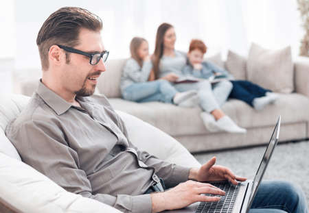 successful man using a laptop in his living room