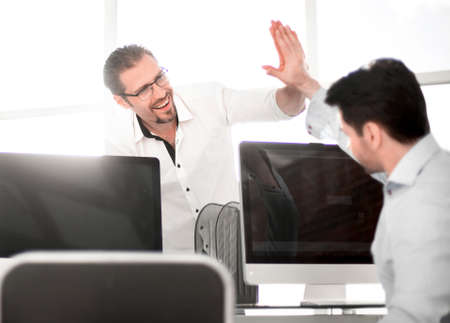 employees give each other a high five over the computer Desk