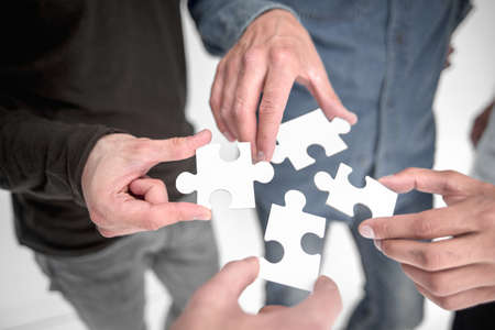 close up. pieces of the puzzle in the hands of young people Stockfoto