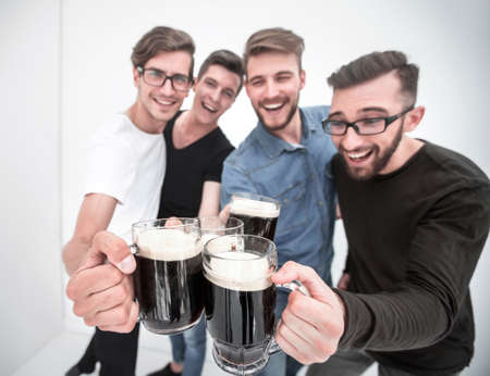 group of happy young men, clinking glasses of beer.