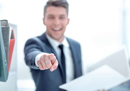 business man with documents showing his finger in the camera on a light background