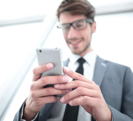 Businessman looking at mobile phone in office