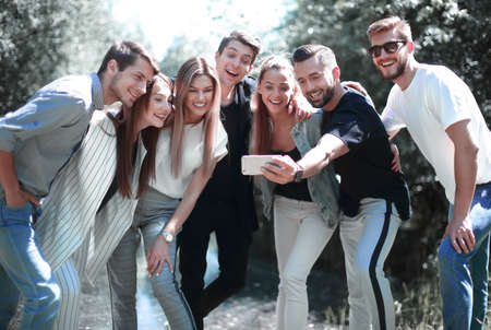 group of friends takes a selfie on the background of the city Park