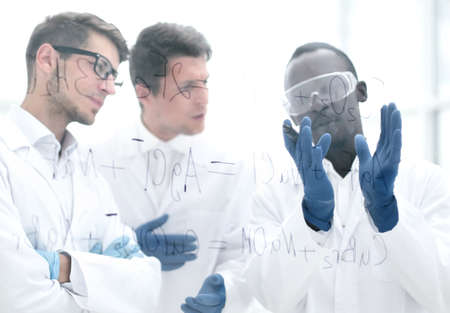 group of scientists talking standing near a glass Board. Stock Photo