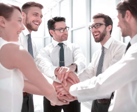 close up.a smiling business team stands with their hands folded together. Foto de archivo - 131725933